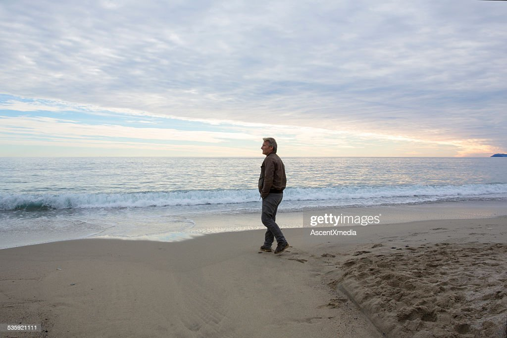 Man walks across beach under dome of clouds, to sea : Stock Photo