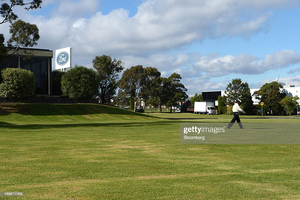 A man walks across the lawn in front of Ford Motor Co.'s Australia head office building in Melbourne, Australia, on Thursday, May 23, 2013. Ford will stop making cars in Australia, nine decades after founder Henry Ford first began building Model Ts in the country, as a surge in the currency undermines the local industry's ability to compete with imports. Photographer: Carla Gottgens/Bloomberg via Getty Images