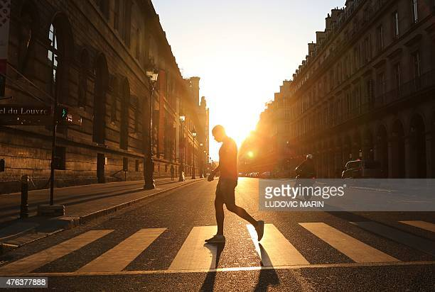 A man walks across the Rivoli street along the Louvre museum at sunset in Paris on June 8 2015 AFP PHOTO / LUDOVIC MARIN