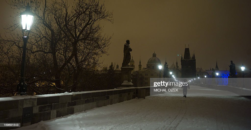 A man walks across the snow covered medieval Charles Bridge early in the morning on January 18, 2013 in Prague .
