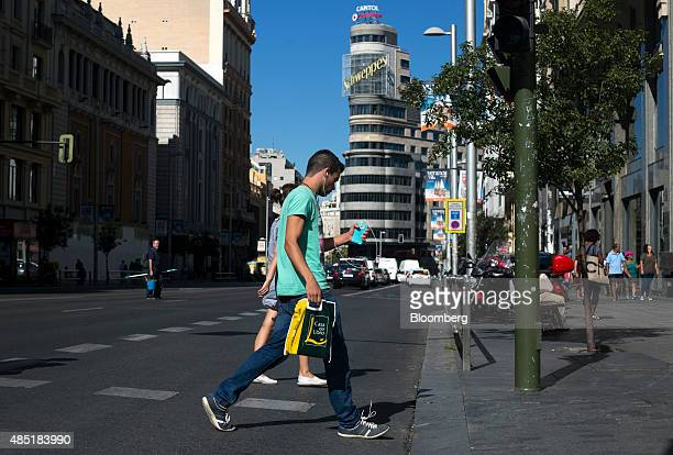 A man walks across the street holding a shopping bag and a smartphone in Madrid Spain on Tuesday Aug 25 2015 The euro has surged almost 4 percent...