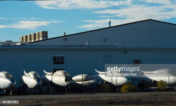 A man walks across the top of a hangar at Mojave Air and Space Port on October 23 2013 in Mojave Ca