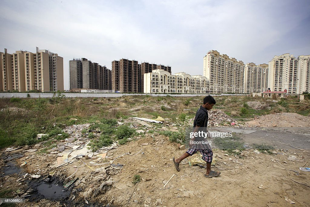 A man walks across wasteland as newly constructed residential buildings stand in the background in Gurgaon, India, on Wednesday, March 26, 2014. Indian stocks rose, sending the benchmark index to a record, after the rupee rose to an eight-month high and sovereign bonds gained on speculation the worlds largest democracy will elect a government capable of reviving economic growth. Photographer: Kuni Takahashi/Bloomberg via Getty Images
