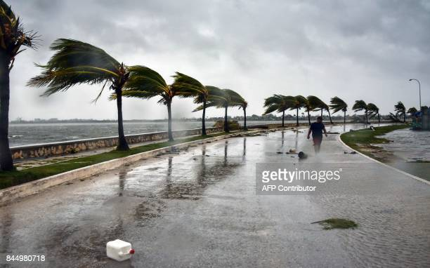 TOPSHOT A man walks against heavy winds after the passage of Hurricane Irma at Caibarien Villa Clara province 330km east of Havana on September 9...