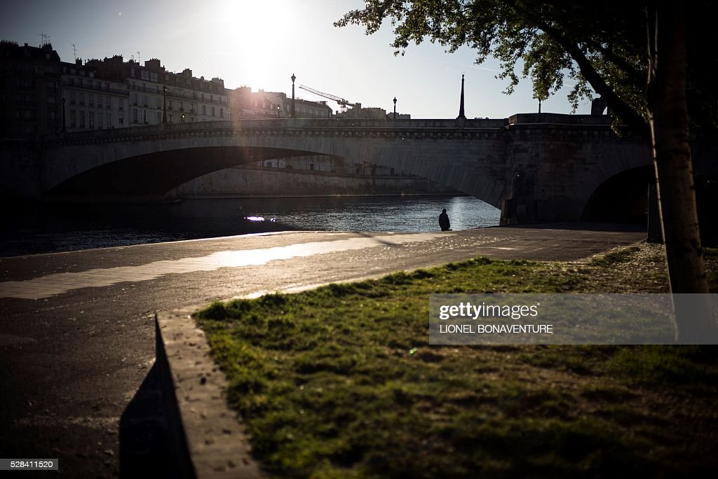A man walks along a bank of the Seine river, on May 5, 2016 in Paris. / AFP / LIONEL