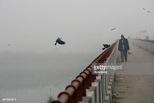 A man walks along a bridge shrouded in haze in New Delhi India on Monday Jan 20 2014 India China and Brazil three of the largest developing nations...
