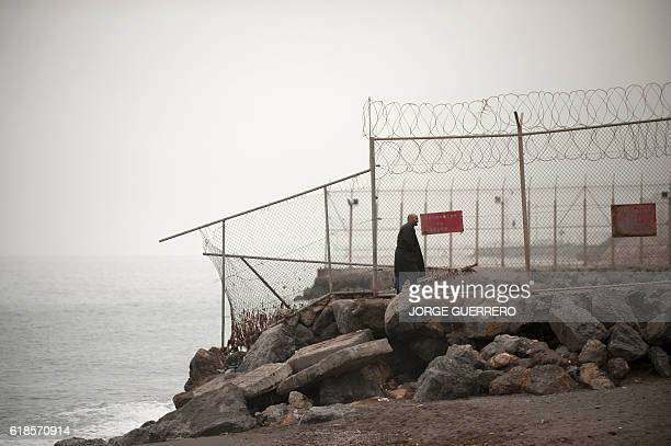 A man walks along a fence in the border separating Morocco and Spain's North African enclave of Ceuta in Ceuta on October 27 2016 / AFP / JORGE...