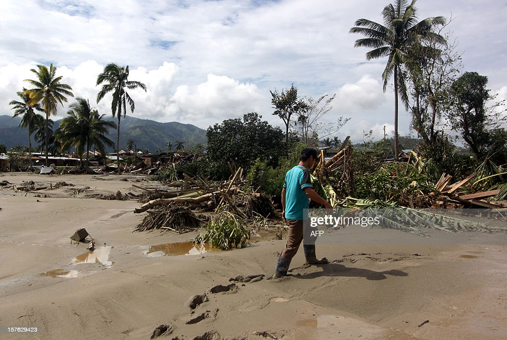 A man walks along a muddy street in the aftermath of Typhoon Bopha in New Bataan, Compostela Valley in the southern Philippines on December 5, 2012. The death toll from a typhoon that ravaged the Philippines jumped to 238 on December 5 with hundreds missing, as rescuers battled to reach areas cut off by floods and mudslides, officials said. AFP PHOTO / Karlos Manlupig