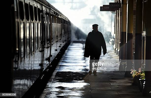 A man walks along a platform past carriages pulled by The Flying Scotsman steam train at Bury Bolton Street rail station in Bury north west England...