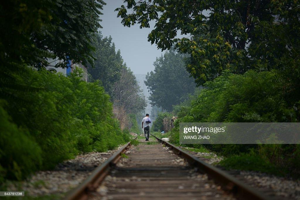 A man walks along a railway track in Beijing on June 30, 2016. / AFP / WANG