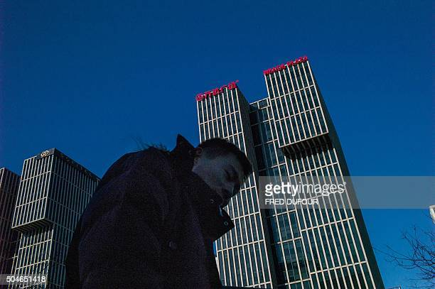 A man walks along a road before the Chinese conglomerate Wanda Group building in Beijing on January 12 2016 Chinese conglomerate Wanda Group is...