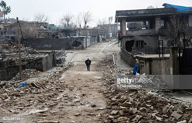 TOPSHOT A man walks along a road damaged in the fighting between government troops and separatist Kurdistan Workers' Party fighters in the Kurdish...