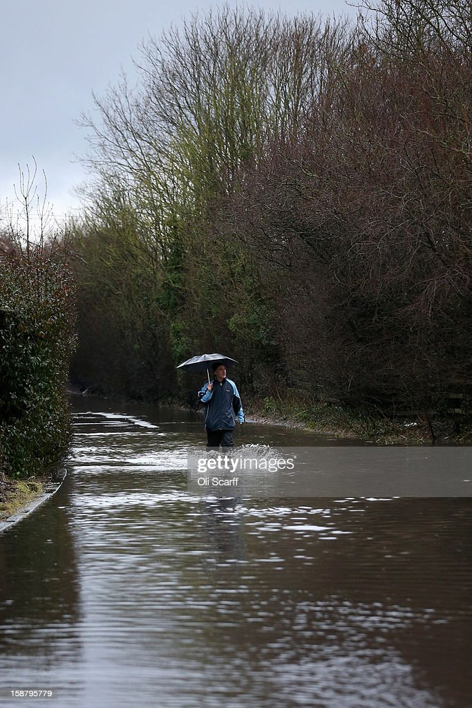A man walks along a road submerged by flood waters from the River Thames on December 29, 2012 in Sonning, England. The Environment Agency has issued widespread flood warnings across the UK whilst the Met Office has predicted further rain forecast for the remainder of 2012, which is likely to be recorded as the wettest year since records began in 1910.