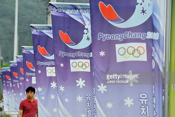 A man walks along a row of banners with the logo of South Korea's mountain resort of Pyeongchang 180 kms east of Seoul on July 7 2011 after the...