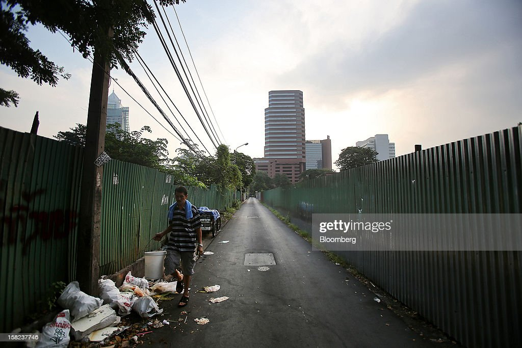 A man walks along a side street between fencing demarcating plots of land off Langsuan road in Bangkok, Thailand, on Tuesday, Dec. 11, 2012. The Crown Property Bureau owns about 41,300 rai (66 square kilometers) of land across the country, about a fifth of which is in Bangkok, according to Aviruth Wongbuddhapitak, an adviser to the CPB who sits on the board of two of its subsidiaries. Photographer: Dario Pignatelli/Bloomberg via Getty Images