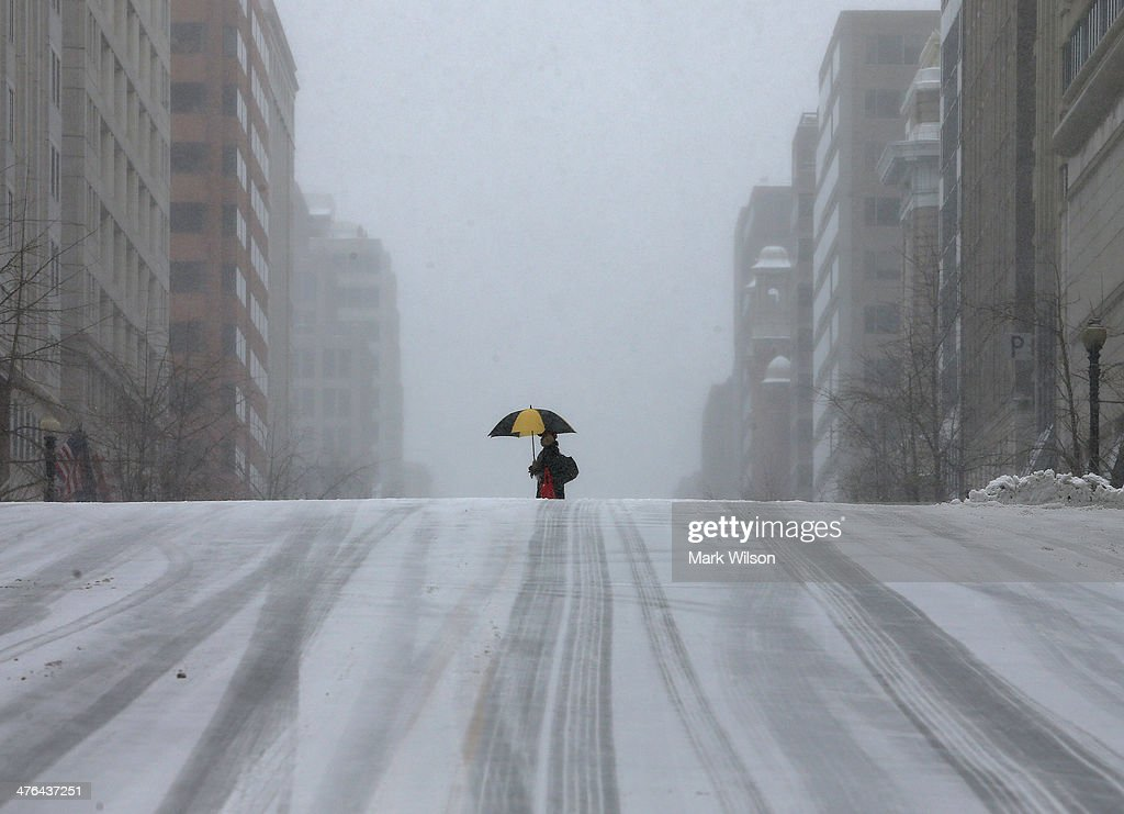 A man walks along a snow covered street, on March 3, 2014 in Washington, DC. The federal governent is closed due to major snowstorm that is expected to dump up to a foot of snow in the Washington area.
