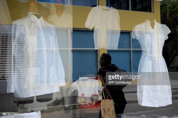 A man walks along a street as his silhouette is reflected in the window of a typical clothing store in Havana on October 27 2017 Almost drowned by...