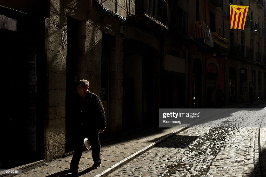 A man walks along a street beneath a pro-independence Catalan flag hanging from a nearby residential building in Girona, Spain, on Thursday, Jan. 31, 2013. Spain's recession deepened more than economists forecast in the fourth quarter as the government's struggle to rein in the euro region's second-largest budget deficit weighed on domestic demand. Photographer: David Ramos/Bloomberg
