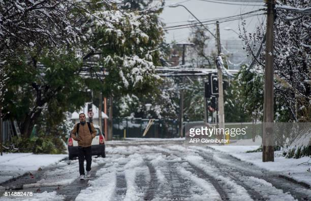A man walks along a street covered with snow in Santiago on July 15 2017 An unusual snowfall the first of such intensity since 2007 surprised the...