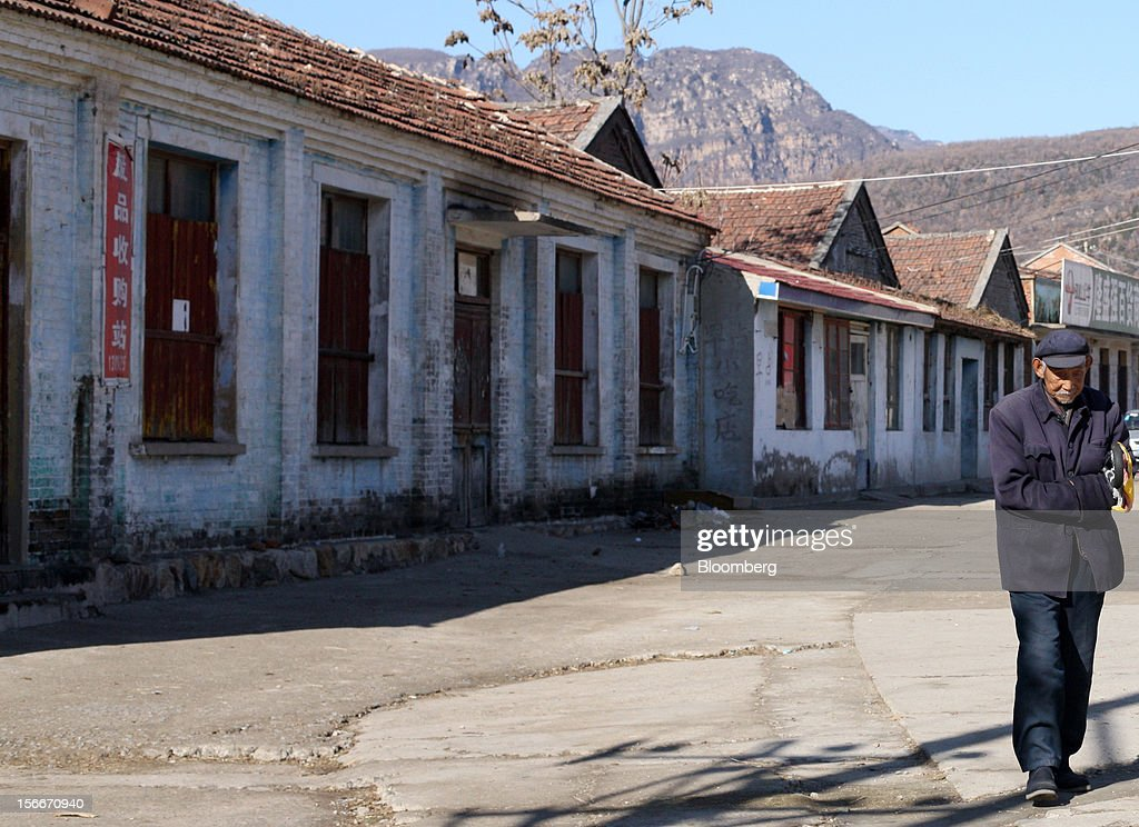 A man walks along a street in Pinggu, on the outskirts of Beijing, China, on Saturday, Nov. 17, 2012. China's gross domestic product slowed to 7.4 percent in the July-September period from a year earlier, the weakest in three years. Photographer: Tomohiro Ohsumi/Bloomberg via Getty Images
