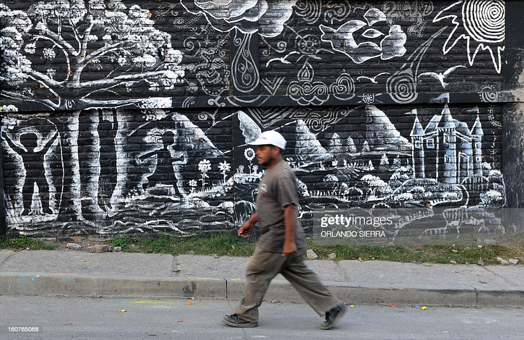 A man walks along a street in the poor community of Las Ayestas, in Tegucigalpa on February 5, 2013. Honduras' notorious street gangs, especially the Mara 18 and the Mara 13 or Salvatrucha, have imposed a curfew and are charging a 'war tax' in some of the capital's poorest sectors -- thing which led the police to deploy more personnel in theses areas. The violent maras are active in murders, extorsion, drug dealing, arms trafficking and other crimes. The United Nations says Honduras, a country plagued by powerful street gangs and drug-related violence, has the world's highest homicide rate. In 2010 it was 82 per 100,000 inhabitants, and rose to 86 in 2011. By comparison, in drug-cartel-plagued Mexico, for instance, the rate was about 18 in 2010. AFP PHOTO/Orlando SIERRA