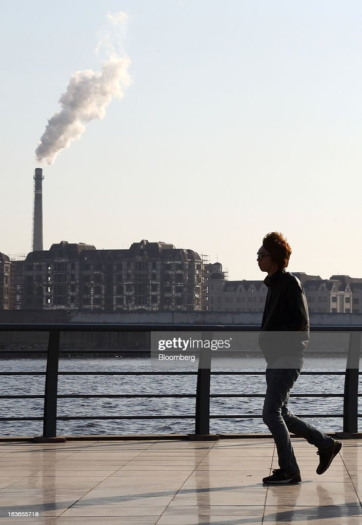 A man walks along a waterfront as steam rises from a chimney in Tianjin, China, on Wednesday, March 13, 2013. China's money-market rate rose to a one-week high after central bank Governor Zhou Xiaochuan said yesterday the nation should be on 'high alert' over inflation. Photographer: Tomohiro Ohsumi/Bloomberg via Getty Images