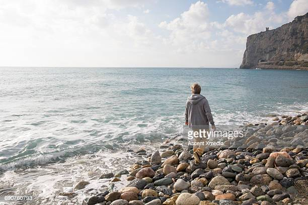 Man walks along coastal rocks, looks to sea