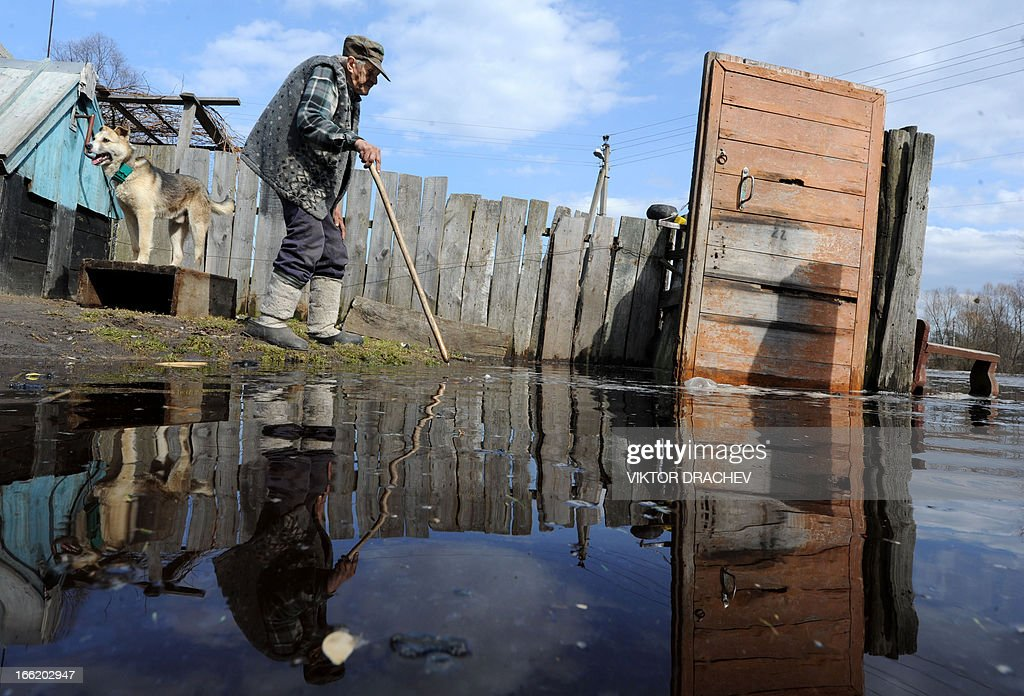A man walks along his yard during spring flood in a village of Snyadin some 300 km south of Minsk, on April 9, 2013. Belarus will take all necessary precautions to minimize the consequences of spring floods, Belarus President Alexander Lukashenko said as he visited Minsk-based Sukno Company on 5 April.