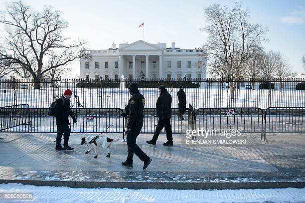 A man walks along Pennsylvania Avenue past Secret Service officers and the White House after the city received a light snow storm overnight January...