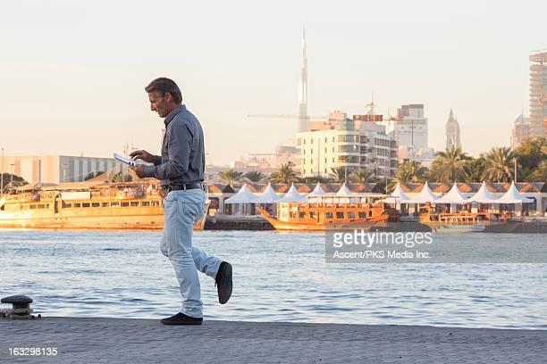 Man walks along river front, using digital tablet