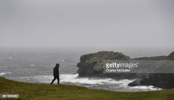 A man walks along St John's Point during Hurricane Ophelia on October 16 2017 in Donegal Ireland The hurricane hit the north west coast of Ireland...