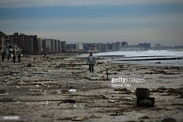 A man walks along the beach in the heavily damaged Rockaway neighborhood in Queens where a large section of the iconic boardwalk was washed away on...