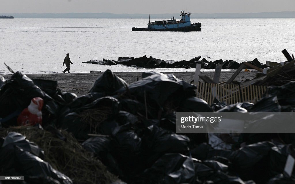 A man walks along the beach past flood debris piled on the beach in the Coney Island neighborhood on November 20, 2012 in the Brooklyn borough of New York City. The Coney Island area was hard hit by Superstorm Sandy.