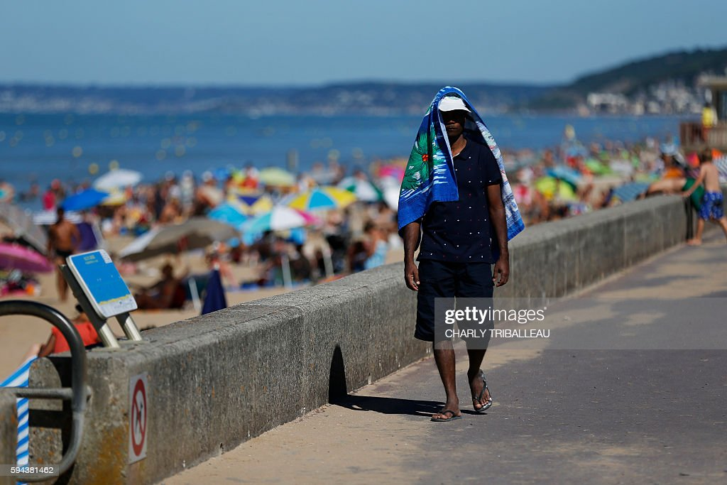 A man walks along the beach with a towel covering his head and shoulders on August 23 2016 in Varaville northwestern France as temperatures soar...