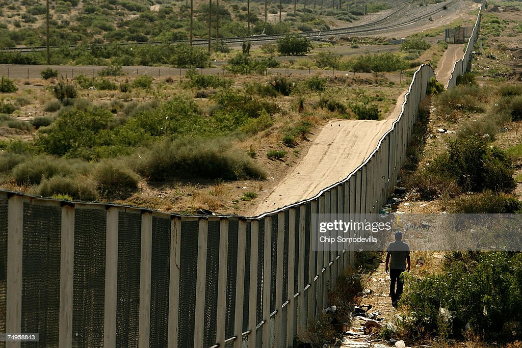 A man walks along the border fence between the US and Mexico on June 29 2007 in the Anapra area of Ciudad Juarez Mexico This area is a popular...