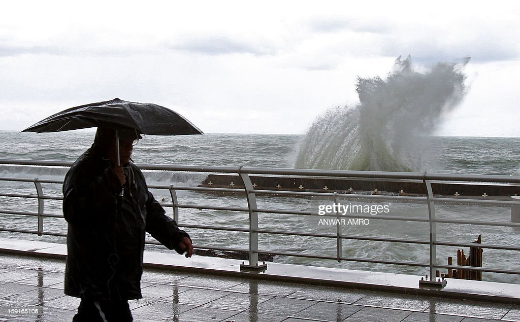 A man walks along the promenade in Beirut as waves crash against the rocks in stormy weather conditions on January 9, 2013. A met office official at Beirut airport said the storm would continue and that lower temperatures would result in snowfall in the mountains as low as 300 metres (1,000 feet). AFP PHOTO/ANWAR AMRO