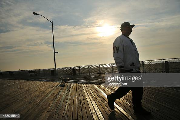 A man walks along the recently repaired boardwalk at Rockaway Beach which was heavily damaged during Hurricane Sandy on October 29 2014 in New York...