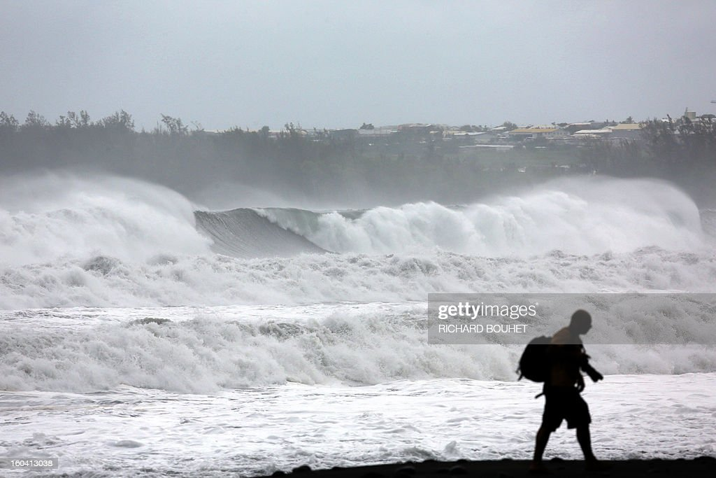 A man walks along the sea on the northwestern coast of French Indian Ocean island of La Reunion on January 31, 2013 near Saint-Paul, as high waves hit the coastline, caused by the cyclone Felleng at 530 Km north of the island. BOUHET