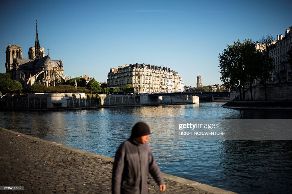 A man walks along the Seine river, on May 5, 2016 in Paris. / AFP / LIONEL