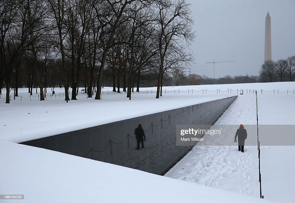 A man walks along the snow covered Vietnam Memorial, on February 13, 2014 in Washington, DC. The east coast was hit with a winter snowstorm with the Washington area recieving up to 8 inches of snow.