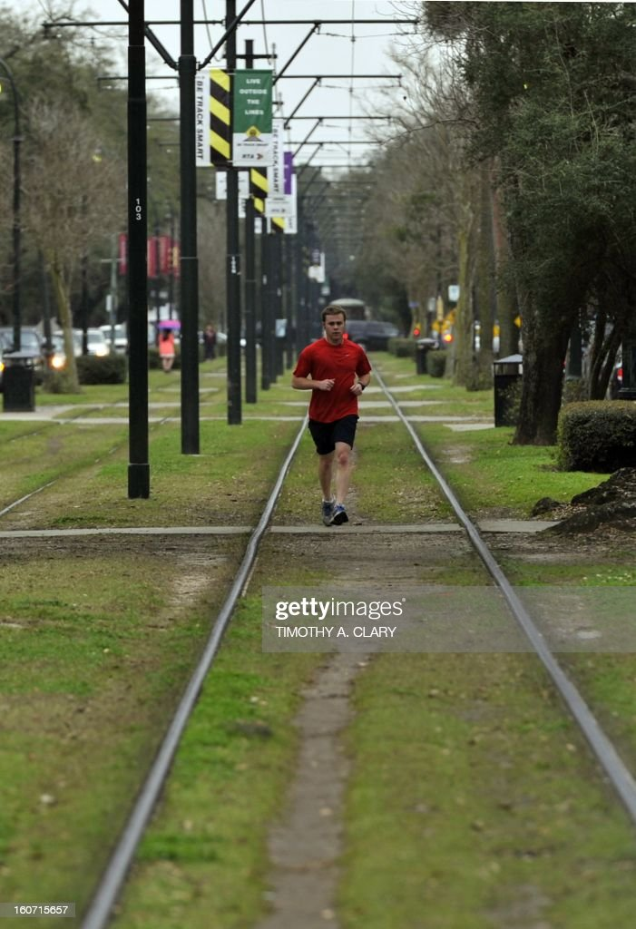 A man walks along the St. Charles line in New Orleans, Louisiana Febuary 4, 2013, which travels from the edge of the French Quarter all the way down beautiful St. Charles Avenue, passing by celebrated restaurants, shops, and hotels. Some destinations of note include the Garden District, Audubon Park. The original line dates back to 1835, and due to its status on the National Register of Historic Places, by federal law the current 'Perley Thomas' streetcars in use must be preserved in time as they existed in 1923. AFP PHOTO / TIMOTHY A. CLARY