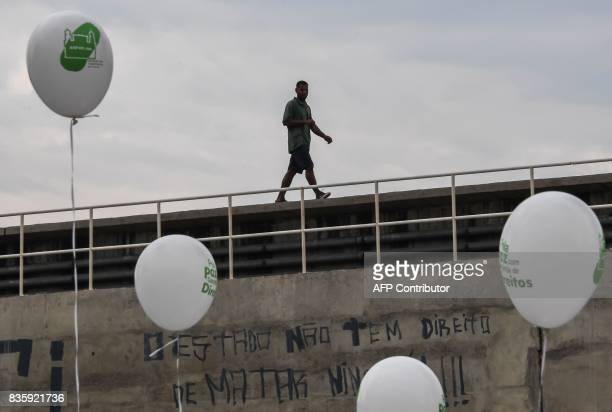 A man walks along the train tracks over a graffiti reading 'The State Has No Right To Kill' during a demonstration staged by residents of Rio de...