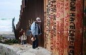 A man walks along the USMexico border wall on February 22 2015 in Tijuana Mexico Senior Republican senators said they expected Congress will avoid a...
