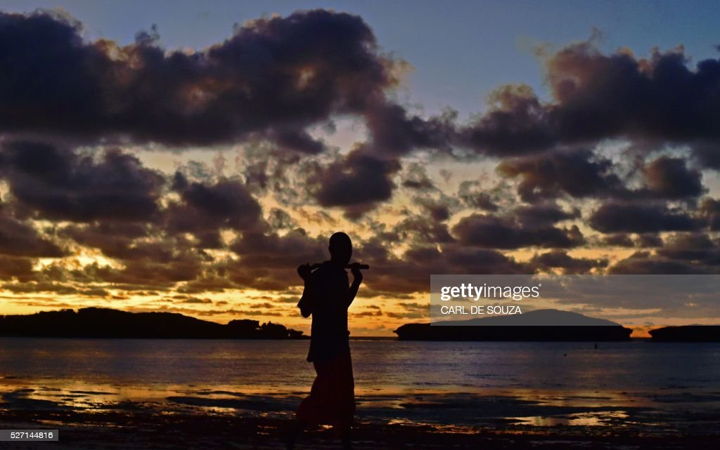 A man walks along Watamu beach at sunrise on May 2, 2016. / AFP / CARL