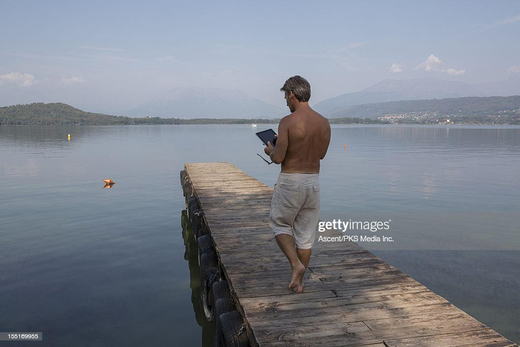 Man walks along wooden wharf, uses digital tablet : Stock Photo
