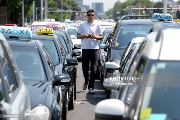 A man walks among Croatian taxi cars parked in a main avenue to perturb traffic in Zagreb on June 21 to protest against controversial competitor...