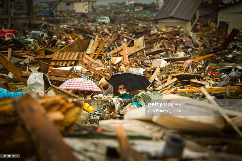 A man walks among debris at Rikuzentakata on March 26, 2011 in Iwate Prefecture, Japan. The 9.0 magnitude strong earthquake struck offshore on March 11 at 2:46pm local time, triggering a tsunami wave of up to ten metres which engulfed large parts of north-eastern Japan, and also damaging the Fukushima nuclear plant and threatening a nuclear catastrophe. The death toll continues to rise with numbers of dead and missing exceeding 20,000 in a tragedy not seen since World War II in Japan.