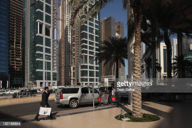 A man walks among new skyscrapers standing in the budding new financial district on October 23 2011 in Doha Qatar Qatar will host the 2022 FIFA World...