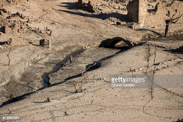 A man walks among the remains of the former town of Mansilla on October 8 2016 after the village emerged from the depths of the Mansilla Reservoir as...