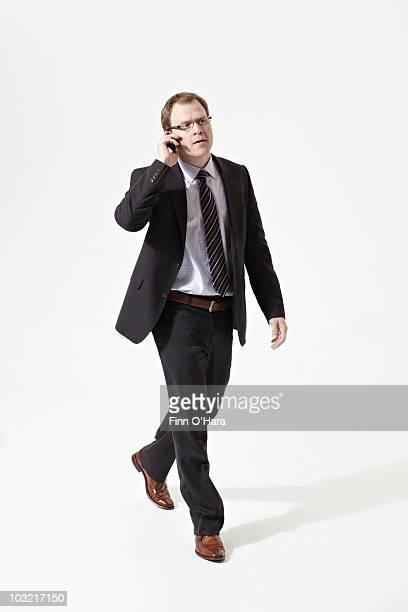 A man walks and talks on his cel phone.